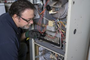 technician-examines-gas-furnace